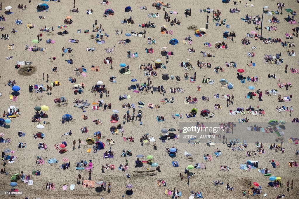 An aerial view taken on July 21, 2013 shows sunbathers crowding on the beach in Scheveningen during a warm summer day. AFP PHOTO / ANP PHOTO / JERRY LAMPEN netherlands out -