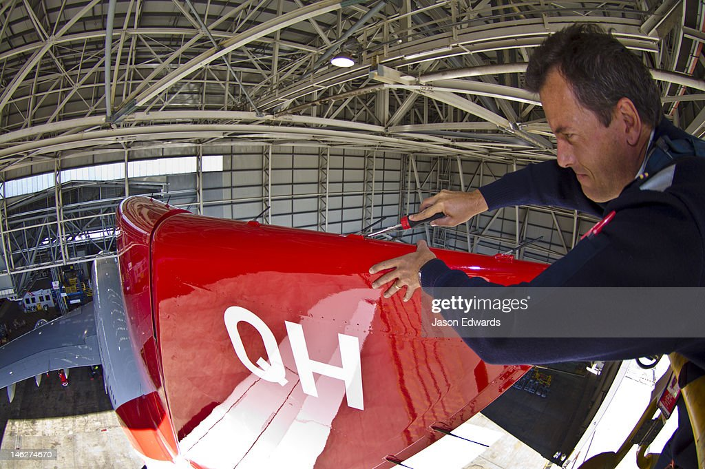 An aeronautical engineer doing maintenance repairs to a jet airliner. : Stock Photo