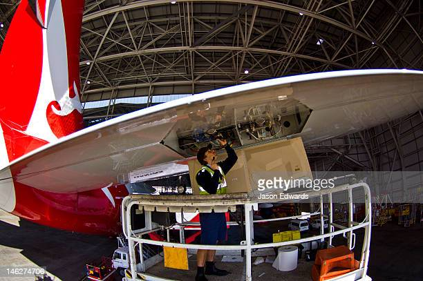 An aeronautical engineer repairs a jet airliner wing from a crane.