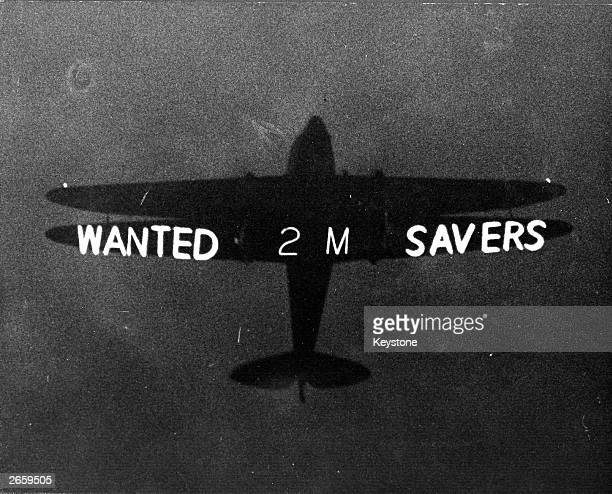 An aeroplane bearing the slogan 'Wanted Two Million Savers' flies over London