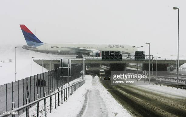 An aeroplane stands stationary during snowfall at the FranzJosephStrauss airport on January 24 2007 in Munich Germany After warmer temperatures than...
