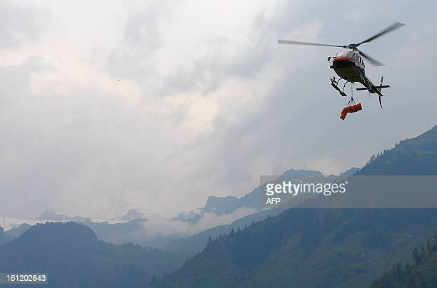 An Aerospatiale Ecureuil AS350 Police helicopter prepares to land in Kaprun carrying the body of a German mountaineer who accidentaly died in the...