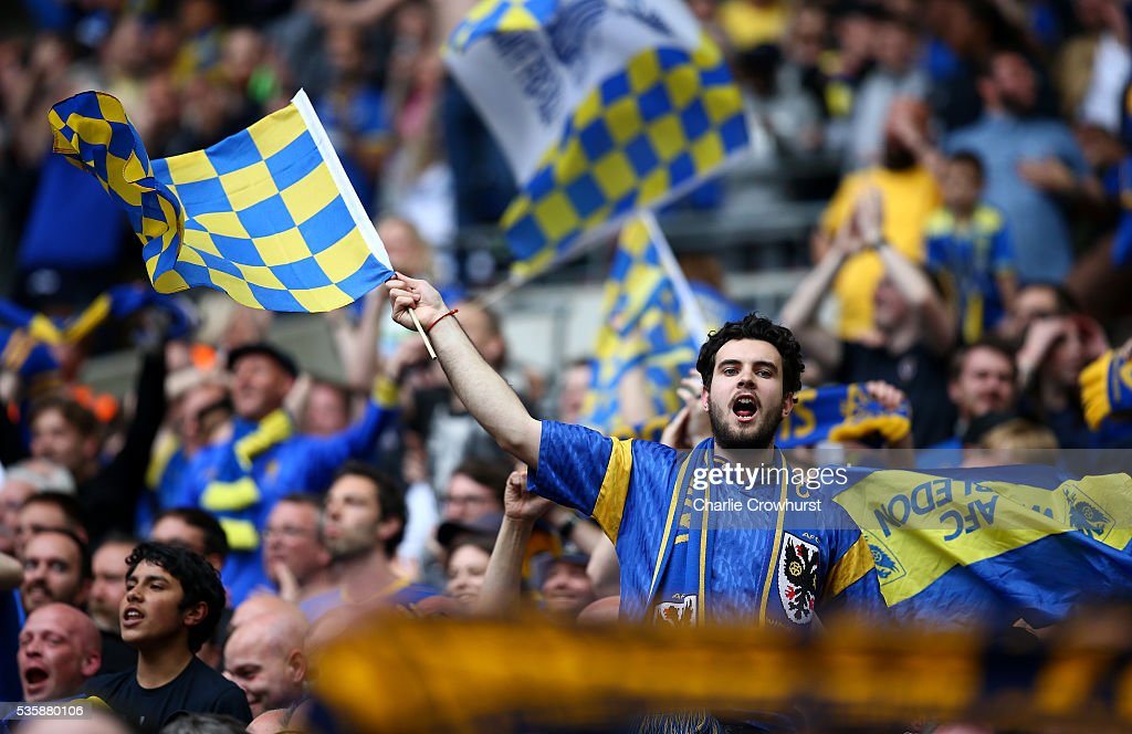 An AFC Wimbledon fan celebrates the teams win and promotion with friends during the Sky Bet League 2 Play Off Final between Plymouth Argyle and AFC Wimbledon at Wembley Stadium on May 30, 2016 in London, England.