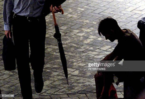 An affluent passerby walks past a destitute man on a street in Hong Kong's Wanchai district 24 August 2000 A global investment bank has said that...