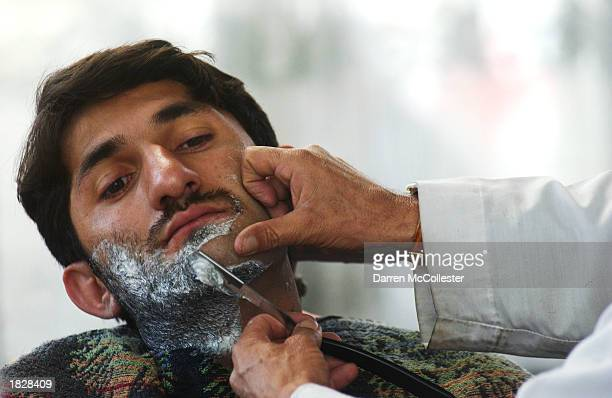 An Afgan man has his beard shaved at the Fazal Mohammad Barber Shop March 4 2003 in Kabul Afghanistan The trimming of beards has become fashionable...