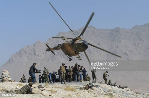 An Afghan Air Force Mi17 helicopter flies past commandos during a military exercise at the Kabul Military Training Centre on the outskirts of Kabul...