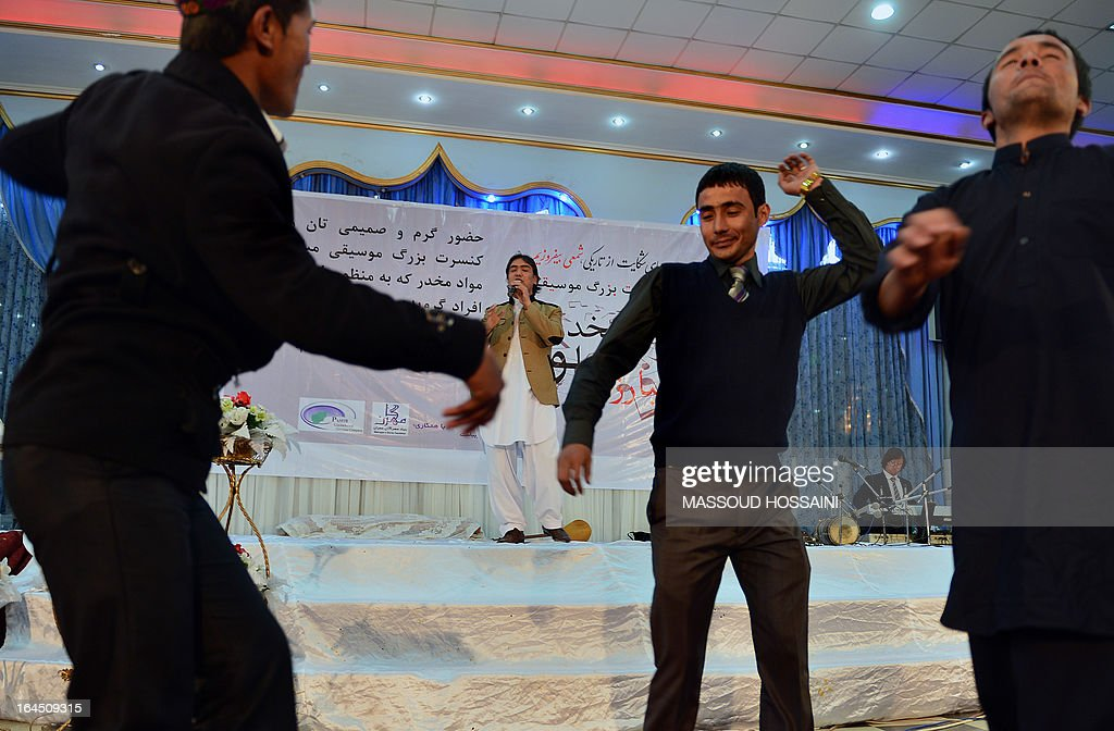 An Afghan artist (C) sings as young men dance during a concert to highlight the Fight against Addiction, arranged by the 'Life Is Beautiful' organisation who work on the rehabilitation of drug addicts, in Kabul on March 24, 2013. According to new reports from the United Nations, there are approximately 272 million drug addicts world-wide with 10 million in the region and one million in Afghanistan, the minister of public health Suraya Dalil said.