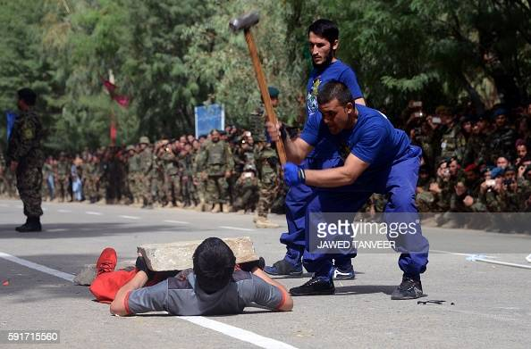 An Afghan athlete lies on iron spokes as colleagues hammer a boulder resting on his body during an event to mark Independence Day in Kandahar...