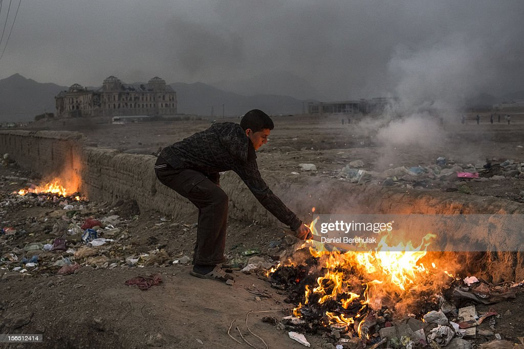An Afghan boy burns household rubbish near the ruined Darul Aman Palace on November 16, 2012 in Kabul, Afghanistan. The Darul Aman, built in the 1920s, was set on fire during the Communist coup of 1978. It was damaged again as rival Mujahedeen factions fought for control of Kabul during the early 1990s. Heavy shelling by the Mujahedeen after the end of the Soviet invasion left the palace a gutted ruin.