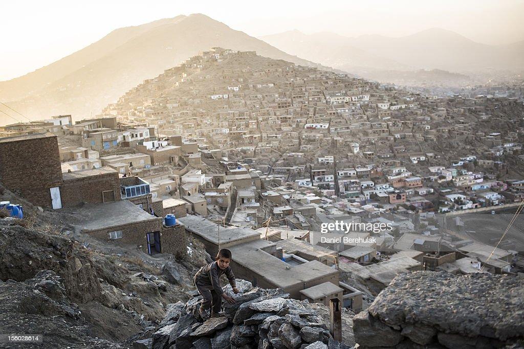An Afghan boy climbs a rock fence on November 11, 2012 in Kabul, Afghanistan.