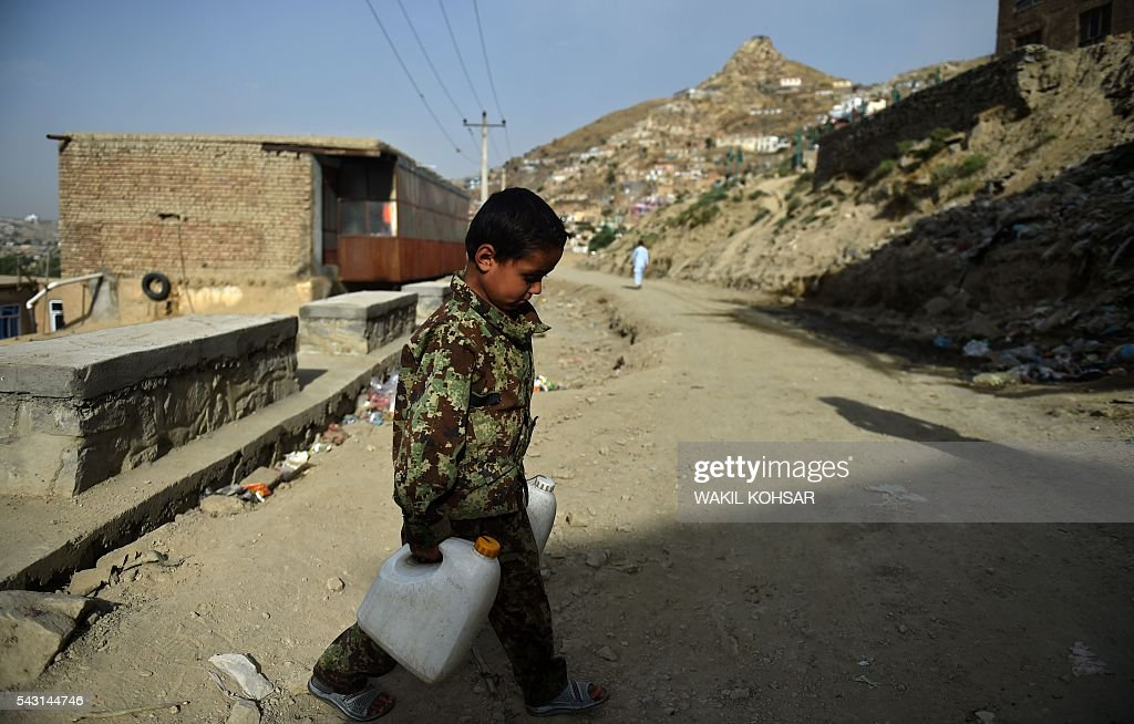 An Afghan boy dressed in military fatigues carries water cans to his home during the Islamic holy month of Ramadan in the old section of Kabul on June 26, 2016 Muslims throughout the world are marking the month of Ramadan, the holiest month in the Islamic calendar during which devotees fast from dawn till dusk. / AFP / WAKIL
