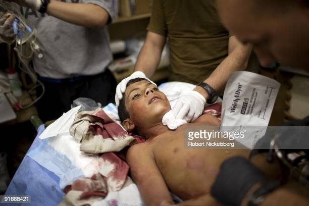 An Afghan boy is treated by US Army medics for a collapsed lung after being hit by shrapnel from a Taliban rocket fired September 6 2009 in Nangalam...
