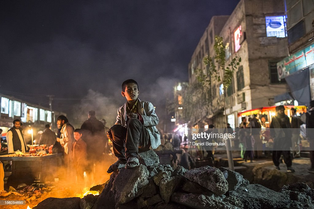 An Afghan boy keeps warm by a fire in the street in the Old City on November 12, 2012 in Kabul, Afghanistan.