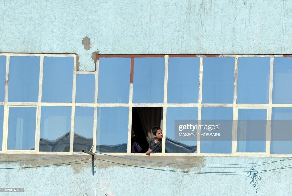 An Afghan boy looks at the site of a clash on the Kabul police headquarters building, through a window in his house, during a clash between Afghanistan forces and Taliban fighters in Kabul on January 21, 2013. Three police officers and three suicide bombers have been killed in an ongoing attack on a police complex in the Afghan capital Kabul, which has already lasted more than six hours, officials said. NATO troops joined a fight against a Taliban suicide squad that stormed a Kabul police headquarters, unleashing a stand-off that lasted for more than five hours. AFP PHOTO/ Massoud HOSSAINI