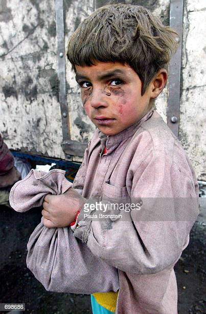 An Afghan boy teary eyed from the coal dust on his face holds his scraps of coal that he collected in his shirt during an International Committee of...