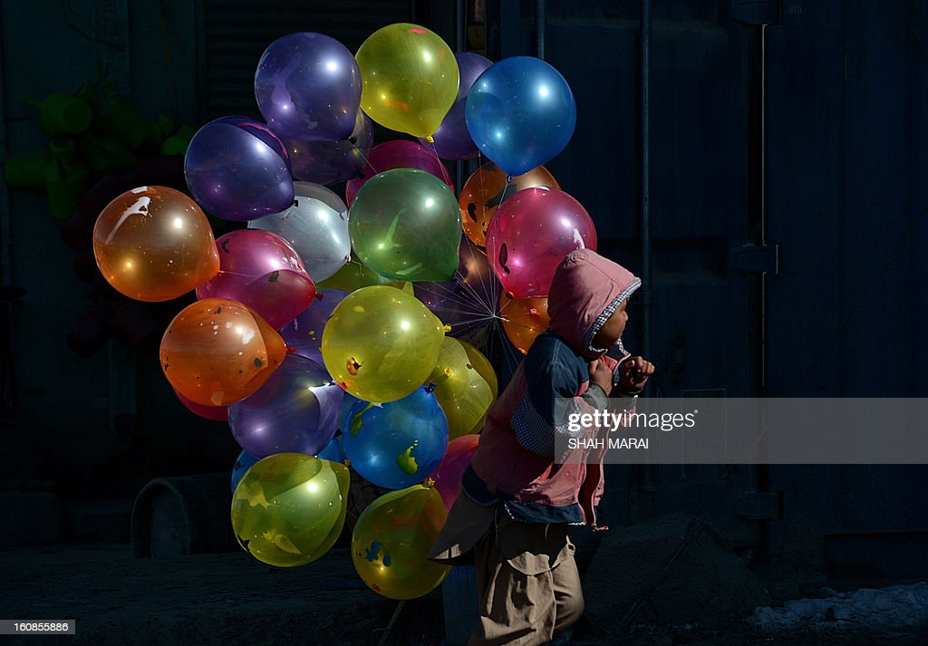 An Afghan boy walks with balloons for sale on a cold winter's day in Kabul on February 7 , 2013. Despite massive injections of foreign aid since the fall of the Taliban in 2001, Afghanistan remains desperately poor with the lowest standards in the world. AFP PHOTO/ SHAH Marai