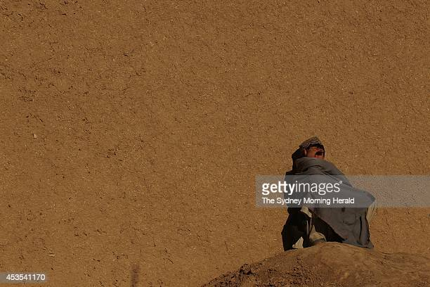An Afghan boy warms himself in the morning sun in the town of Mirabad in Uruzgan Province Afghanistan January 23 2013