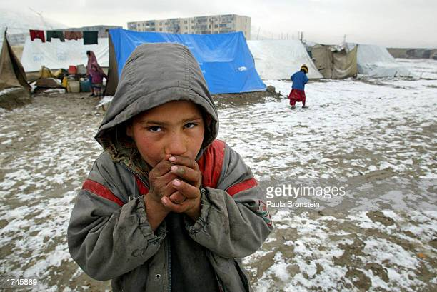 An Afghan boy warms his hands at a tented camp during the first snowfall this winter January 26 2003 on the outskirts of Kabul Afghanistan There are...