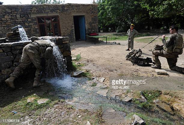An Afghan boy watches US soldiers from Viper Company 126 Infantry cool down with water from an irrigation pump during a foot patrol in Sabari...