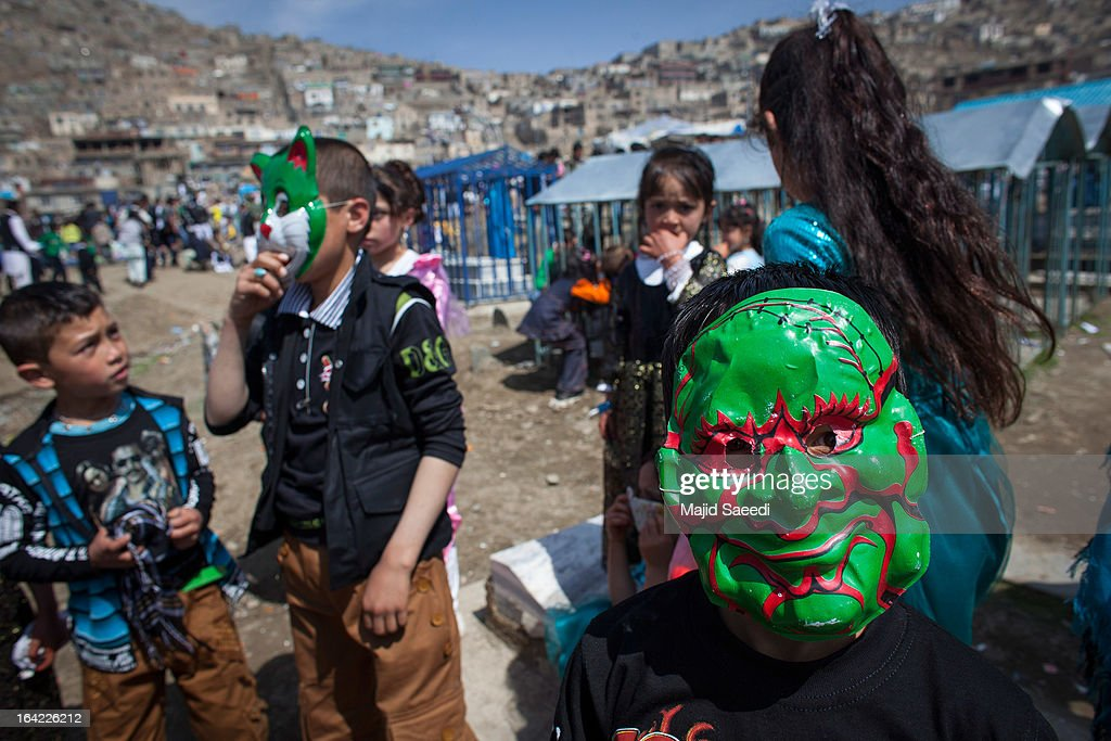 An Afghan boy wears a mask as he plays near the Sakhi shrine, which is the centre of the Afghanistan new year celebrations during the Nowruz festivities on March 21, 2013 in Kabul, Afghanistan. Nowruz is an ancient festival which marks the beginning of the spring equinox and the start of the year in the Iranian calendar, which this coming year will be 1392.