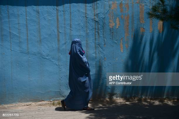 TOPSHOT An Afghan burqaclad woman carries a child as she walks along a road in Herat Province on July 25 2017 / AFP PHOTO / HOSHANG HASHIMI