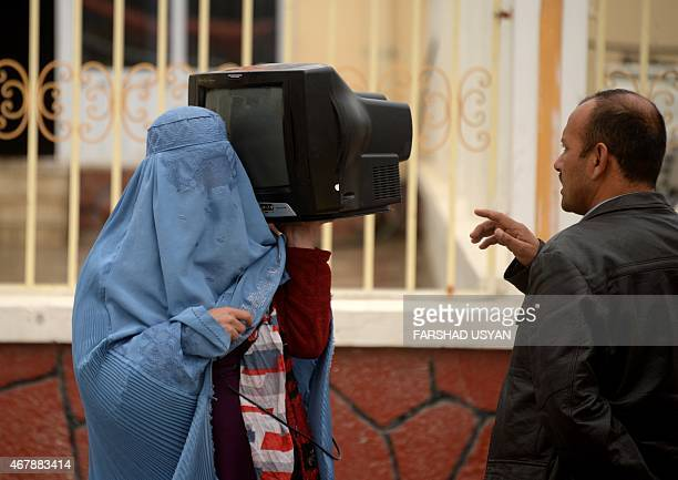 An Afghan burqaclad woman vendor holds a television over her shoulder as she negotiates a sale on the street in Mazarisharif on March 28 2015 AFP...