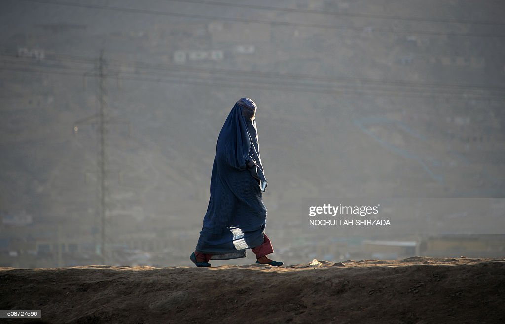 An Afghan burqa-clad woman walks along a road on the outskirts of Kabul on February 6, 2016. AFP PHOTO / Noorullah Shirzada / AFP / Noorullah Shirzada