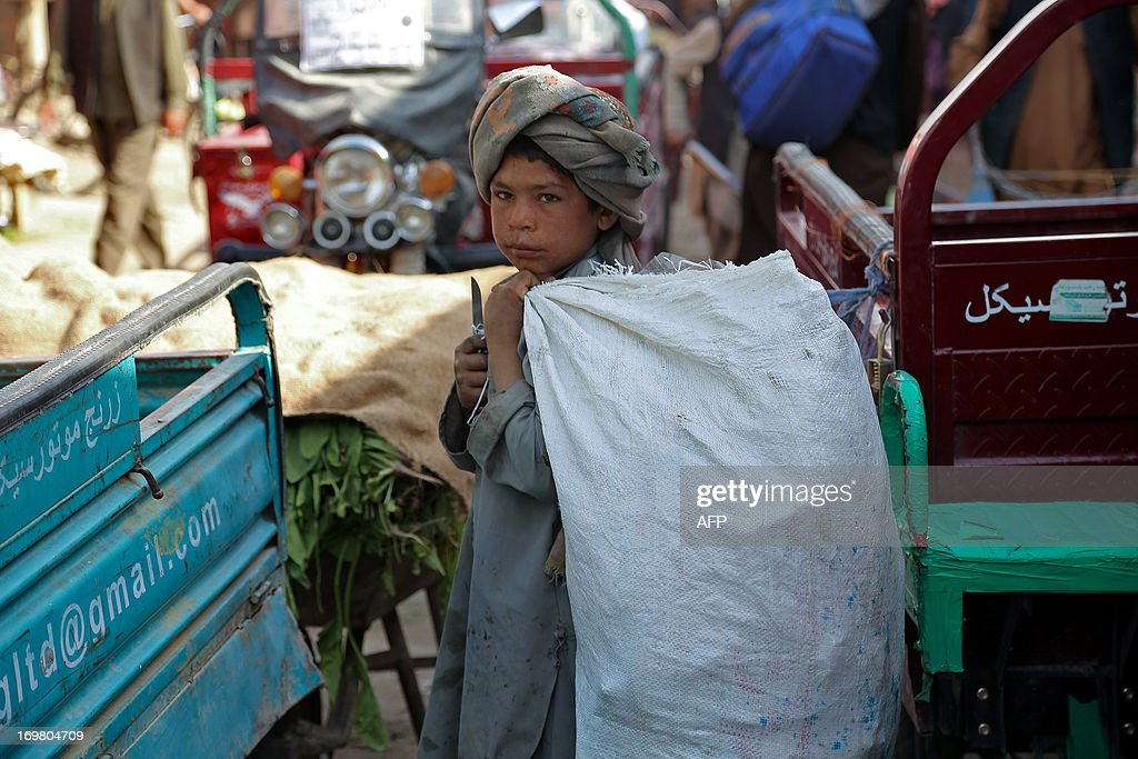 An Afghan child carries a bag as he looks for recyclable items in Ghazni on June 2, 2013, a day after Children's Day. Tens of thousands of children in Afghanistan, driven by poverty, work on the streets of the war-torn country's cities and often fall prey to Taliban bombings and other violence, as well as abuse. AFP PHOTO/Rahmatullah ALIZADA