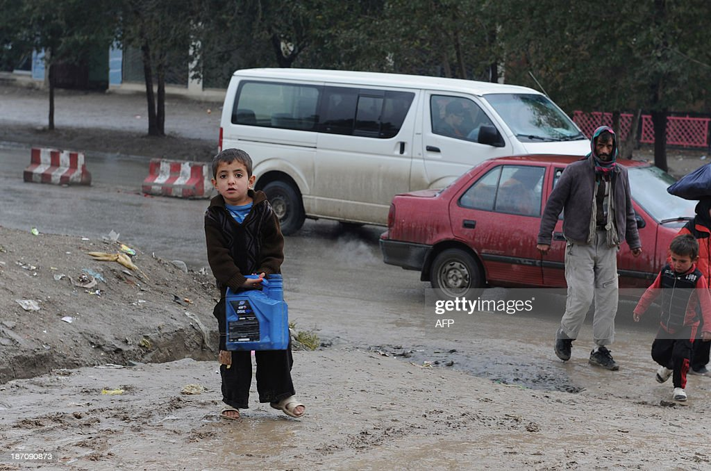 An Afghan child carries water through his neighbourhood on a rainy day in Kabul on November 6, 2013. Despite massive injections of foreign aid since the fall of the Taliban in 2001, Afghanistan remains desperately poor as it attempts to recover from decades of conflict. AFP PHOTO / Farshad USYAN