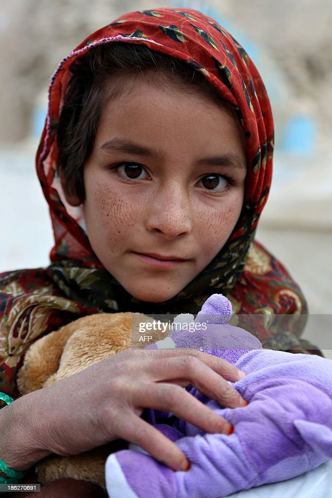An Afghan child holds stuffed toys given to her by Afghan National Army soldiers during a goodwill drive in Ghazni on October 29, 2013. Despite billions of dollars in Western development aid, the United Nations says half of Afghanistan's estimated population of 30 million live below the poverty line in what remains one of the world's poorest countries. AFP PHOTO/ Rahmatullah ALIZADA