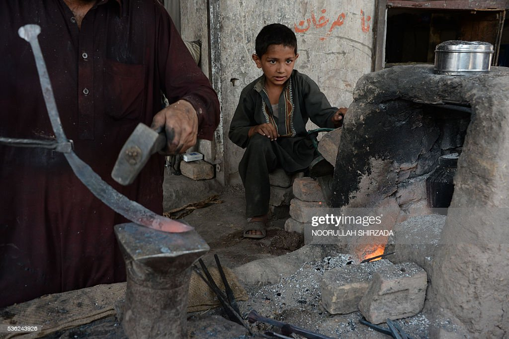 An Afghan child labourer looks on as he works at a blacksmiths shop on the outskirts of Jalalabad, eastern Nangarhar province, during Children's Day on June 1, 2016. Tens of thousands of children in Afghanistan, driven by poverty, work on the streets of the war-torn country's cities and often fall prey to Taliban bombings and other violence, as well as abuse. / AFP / NOORULLAH
