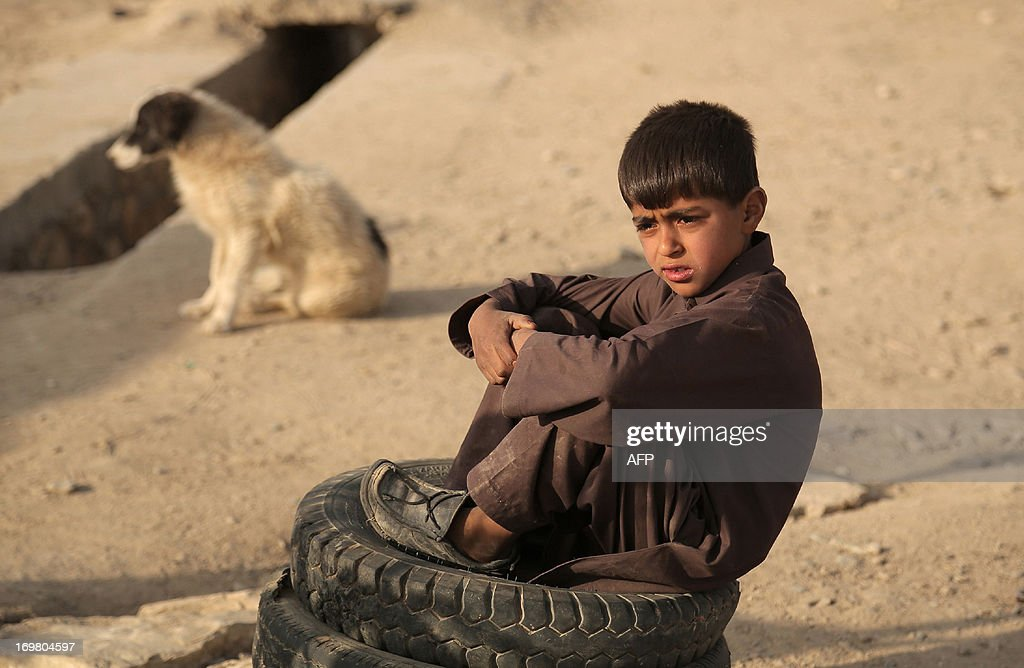 An Afghan child labourer rests as he works in a tire puncture shop in Ghazni on June 2, 2013. Tens of thousands of children in Afghanistan, driven by poverty, work on the streets of the war-torn country's cities and often fall prey to Taliban bombings and other violence, as well as abuse. AFP PHOTO/ Rahmatullah ALIZADA