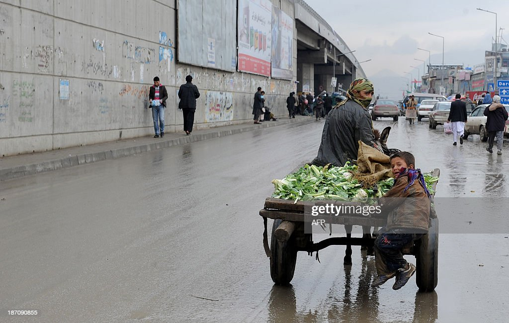 An Afghan child labourer rides on a cart as he works with his brother on a rainy day in Kabul on November 6, 2013. Despite massive injections of foreign aid since the fall of the Taliban in 2001, Afghanistan remains desperately poor as it attempts to recover from decades of conflict. AFP PHOTO / Farshad USYAN