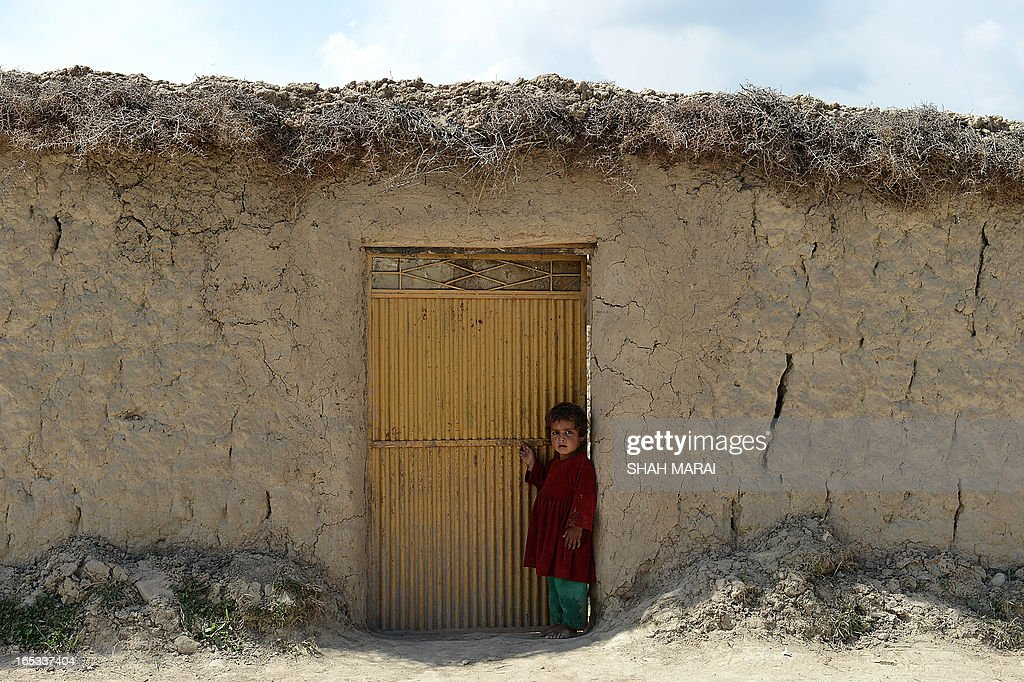 An Afghan child looks on as she stands beside a door made from metal on a compound in Qarabagh district, north of Kabul on April 3, 2013. Village doors in Qarabagh district are made from a variety of scavenged material and are often the only splash of individuality and colour in a drab, beige landscape where one compound looks almost identical to the next. AFP PHOTO/ SHAH Marai