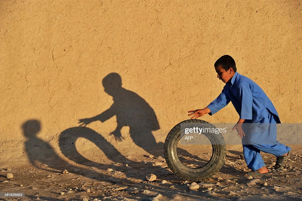 An Afghan child plays with a tire along a street in a village on the outskirts of Jalalabad on March 30, 2014. The literacy rate in Afghanistan is about 30 percent and about 42 percent of the country's population is under the age of 14. According to UNICEF more boys than girls attend classes in primary school in Afghanistan.