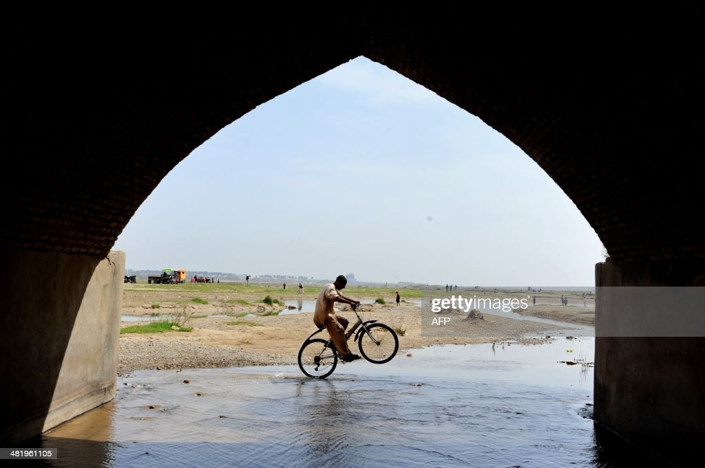An Afghan child plays with his bicycle at the Heri Rud river during 'Sizdeh Bedar' celebrations on the 13th day of Nowruz in the outskirts of the northwestern city of Herat on April 2, 2014. Nowruz is the new year according to the Persian solar calendar and is a Zoroastrian tradition, still celebrated by Iranians, Afghans and Tajiks.