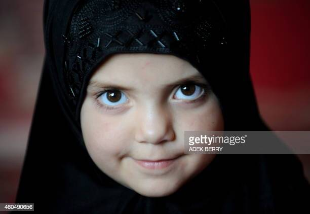 An Afghan child poses for a picture during a reading Koran class at an Islamic school in Kabul on September 4 2011 Women's rights in Afghanistan risk...