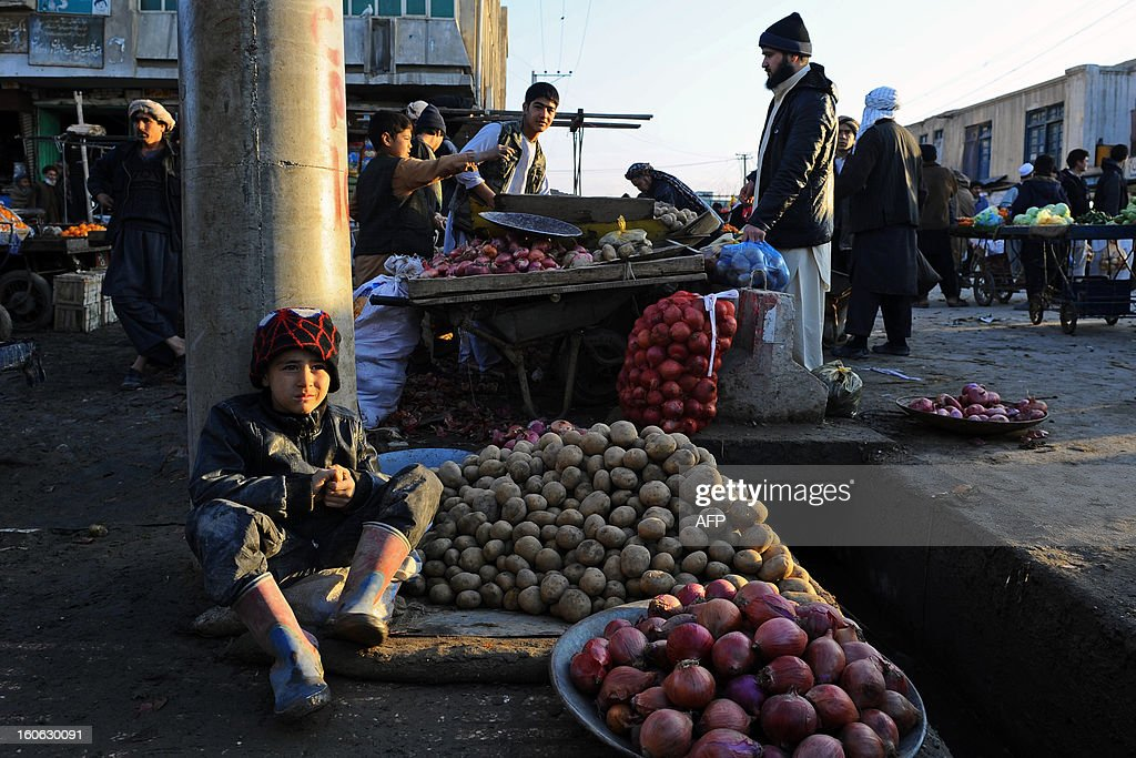 An Afghan child sells potatoes on a street corner in Mazar-i-Sharif, capital of Balkh province, on February 2, 2013. Once known as the 'mother of cities,' the ancient city of Balkh was a popular destination along the ancient Silk Route. Balkh was destroyed by Mongol conqueror Genghis Khan during his rule, with the city's ruins remaining as a tourist attraction today. AFP PHOTO/ Qais Usyan