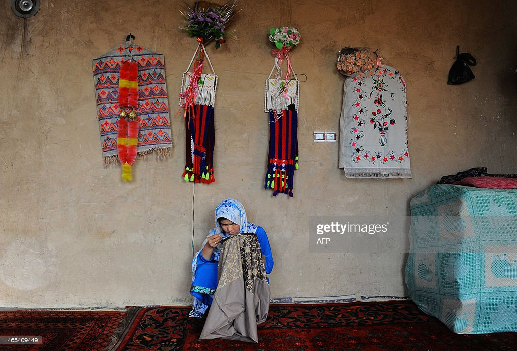 An Afghan child sews fabric at a traditional carpet factory in Herat on January 27, 2014. Some nine million Afghans or 36 percent of the population are living in 'absolute poverty' while another 37 percent live barely above the poverty line, according to a UN report. AFP PHOTO/Aref Karimi