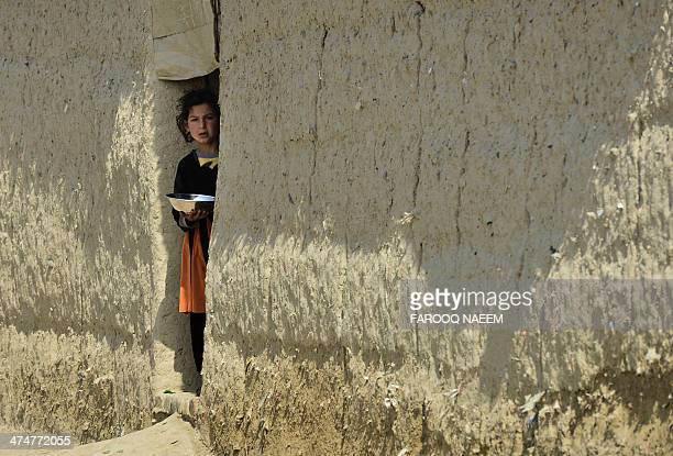 An Afghan child stands in the door to her home at a refugee camp in Haripur on February 25 2014 The Pakistani government in collaboration with the UN...