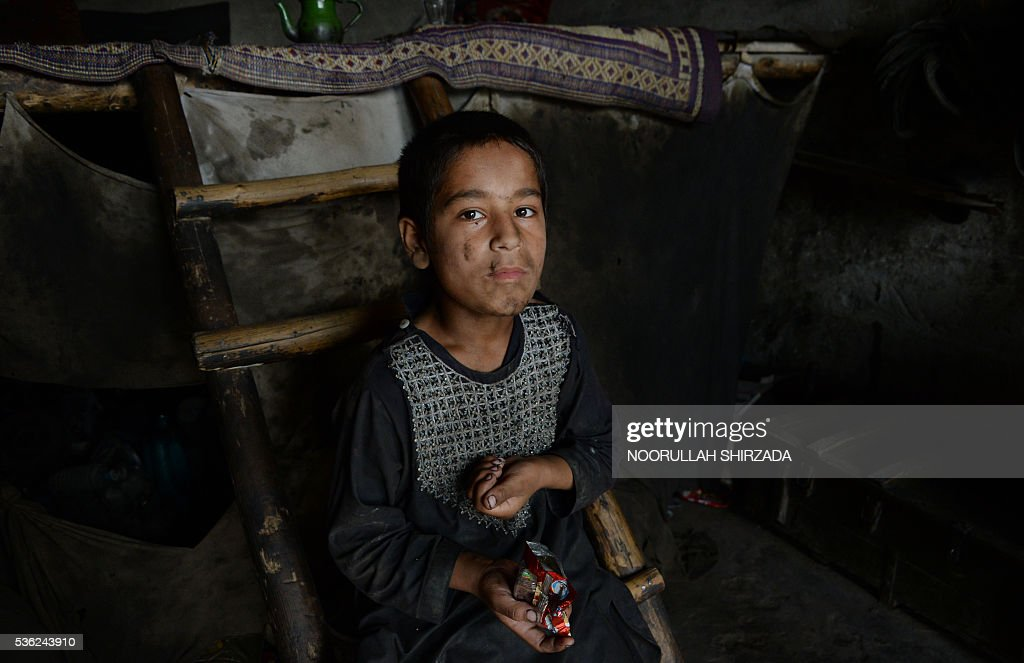 An Afghan child takes rest from his work at a mechanics shop in Jalalabad, eastern Nangarhar province, during Children's Day on June 1, 2016. Tens of thousands of children in Afghanistan, driven by poverty, work on the streets of the war-torn country's cities and often fall prey to Taliban bombings and other violence, as well as abuse. / AFP / NOORULLAH