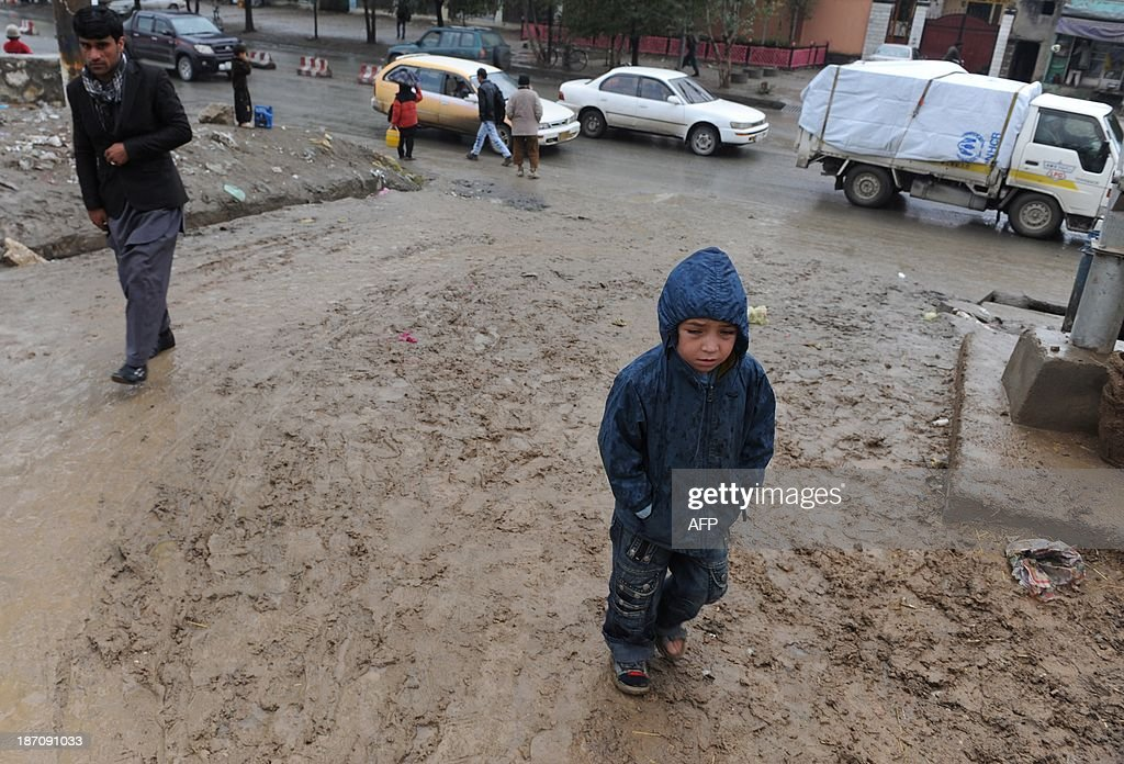 An Afghan child walks through his neighbourhood on a rainy day in Kabul on November 6, 2013. Despite massive injections of foreign aid since the fall of the Taliban in 2001, Afghanistan remains desperately poor as it attempts to recover from decades of conflict. AFP PHOTO / Farshad USYAN