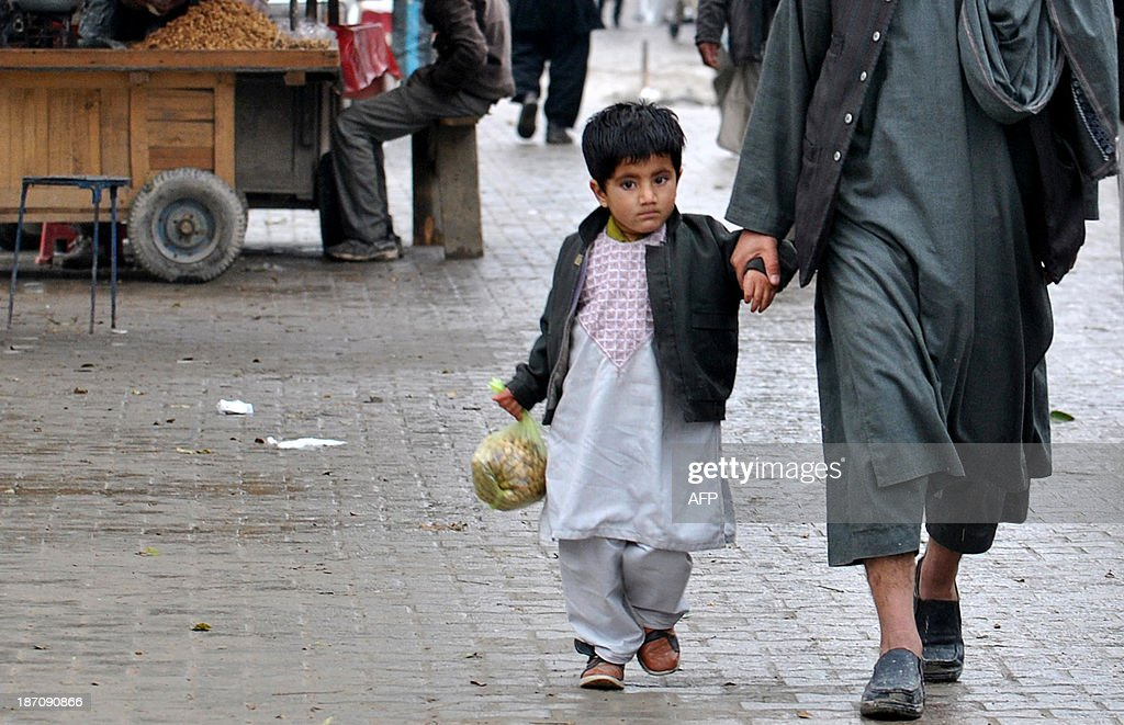 An Afghan child walks with his father in a rainy day in Kabul on November 6, 2013. Despite massive injections of foreign aid since the fall of the Taliban in 2001, Afghanistan remains desperately poor as it attempts to recover from decades of conflict. AFP PHOTO / Farshad USYAN