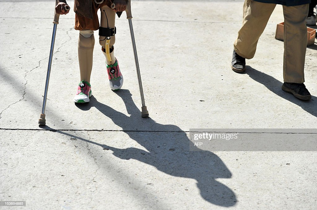 An Afghan child who has lost his legs in a land mine explosion in Bagram District walks with the aid of crutches at The International Red Cross Centre (ICRC) in Kabul on October 8, 2012. The Afghan government could implode after NATO troops pull out in 2014, particularly if presidential elections are fraudulent, a report by the International Crisis Group said. AFP PHOTO/JAWAD JALALI
