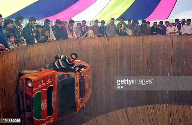 An Afghan circus performer drives a car on a ' Wall of Death' at a fair on the third day of Eid alAdha in Jalalabad on October 28 2012 Afghans...