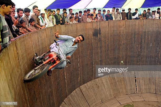 An Afghan circus performer rides a motorcycle on the ' Wall of Death' at a fair on the second day of Eid alFitr in Jalalabad on August 9 2013 Muslims...