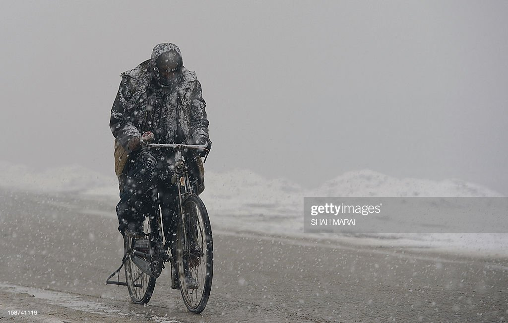 An Afghan commuter rides his bicycle as snow falls in Kabul on December 27, 2012. As winter sets in across Central Asia, many Afghans struggle to provide adequate food and shelter for their families. AFP PHOTO/ SHAH Marai