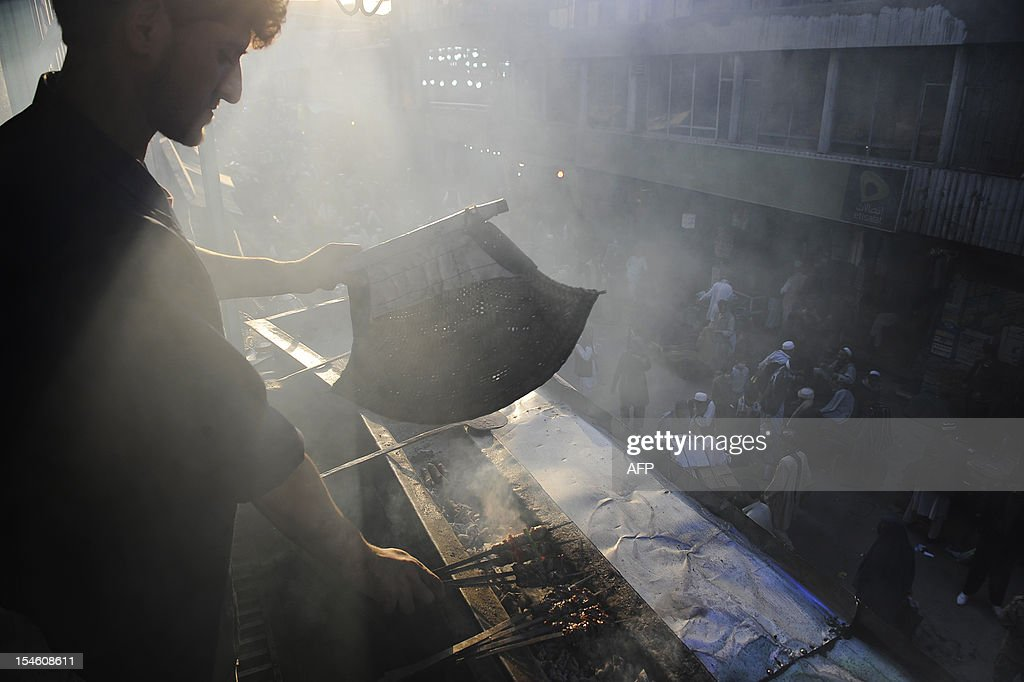 An Afghan cook fans kebabs over a grill in downtown Kabul on October 23, 2012, ahead of the Muslim feast of Eid al-Adha. Eid al-Adha (the Festival of Sacrifice) is celebrated throughout the Muslim world as a commemoration of Abraham's willingness to sacrifice his son for God. The festival falls on the tenth day of Zulhijjah, the final month of the Muslim Calendar and cows, camels, goats and sheep are traditionally slaughtered on the holiest day.