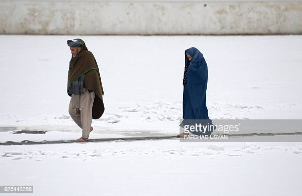 TOPSHOT An Afghan couple walk through the snow in the courtyard of the the famous Blue Mosque in Mazarisharif on Nov 24 2016 / AFP / Farshad USYAN