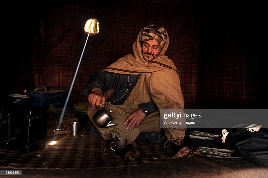 An Afghan customer pours a cap of tea in a traditional tea house in Herat on December 31, 2012. Over a third of Afghans are living in abject poverty, as those in power are more concerned about addressing their vested interests rather than the basic needs of the population, a UN report said. AFP PHOTO/ Aref Karimi